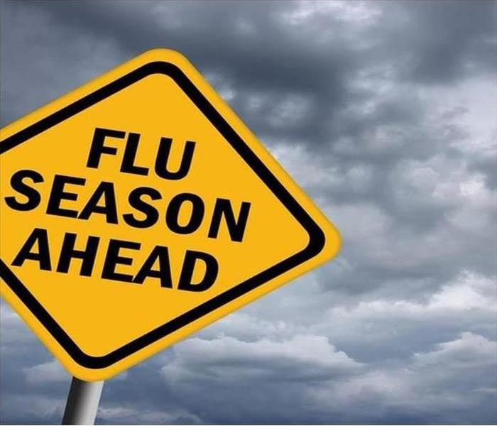 a yellow yield sign with a words reading out flu season ahead